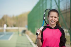Girl with tennis racket smiles after playing sports with braces