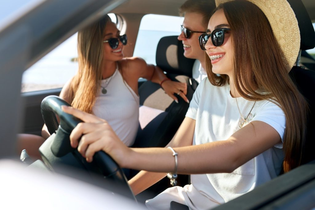 Girl with braces smiling on road trip with friends