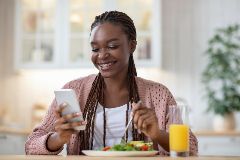Woman with braces smiling while eating lunch